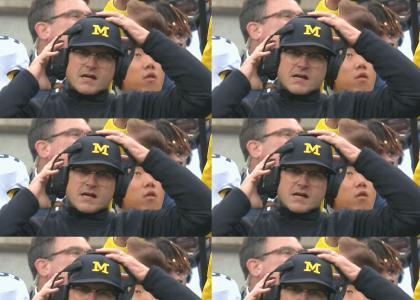Jim Harbaugh adjusts his headset